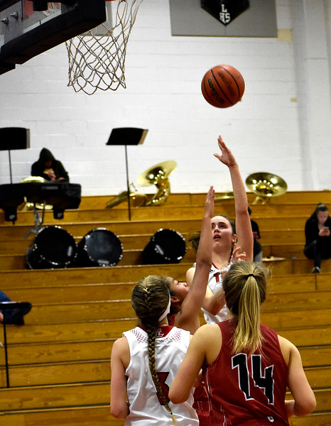 Loveland's (13) Claira Gilchrist attempts a shot at the three-point line before Fairview's (14) Izzy Munson and (3) Adaya Richmond can block during their game on Tuesday, Feb. 13, 2018 at oveland High School in Loveland. Photo by Thieng Mai/Loveland Reporter-Herald.