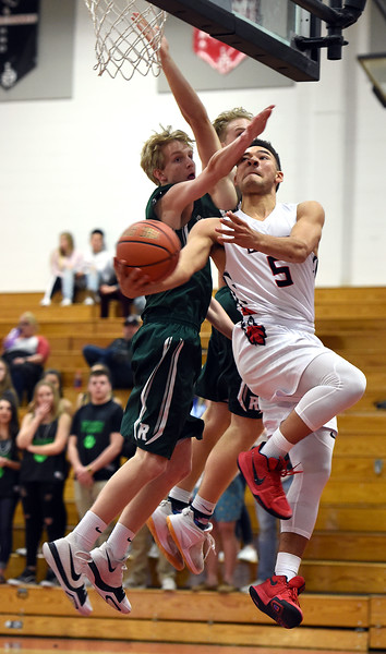 Loveland's (5) Dorian Berg Harry goes up for a shot past Fossil Ridge's (23) Blake Bodnar and (30) Calvin Marley during their game Tuesday, Jan. 9, 2018, at Loveland High School.  (Photo by Jenny Sparks/Loveland Reporter-Herald) fr23 fr30