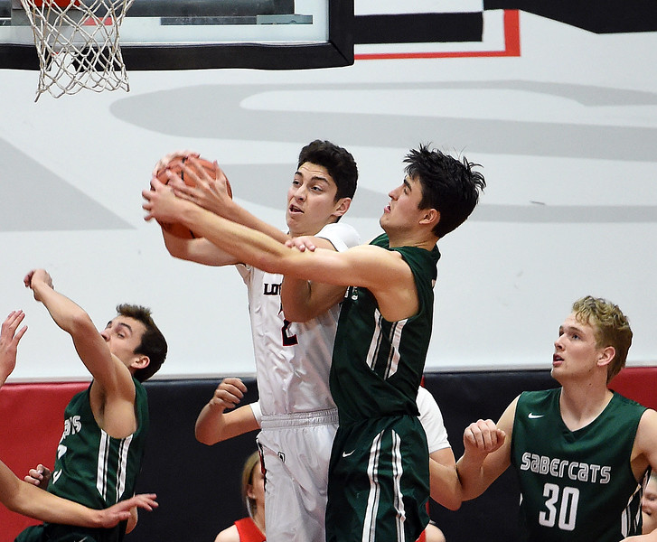 Loveland's (2) Avery Rembao and Fossil Ridge's (5) Brandon Lambrecht go up for a rebound during their game Tuesday, Jan. 9, 2018, at Loveland High School.  (Photo by Jenny Sparks/Loveland Reporter-Herald) 2 5