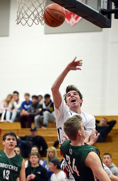. Loveland\'s (21) John Nyenhuis goes up for a shot past Fossil Ridge\'s (34) Ethan Henderson during their game Tuesday, Jan. 9, 2018, at Loveland High School.  (Photo by Jenny Sparks/Loveland Reporter-Herald)  21