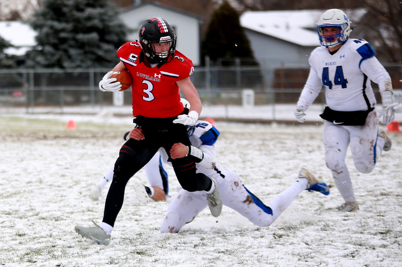 Loveland's (3) Zach Weinmaster runs with the ball as Fruita Monument's (16) Brody Swenson and (44) Treyton Queen go after him on Saturday's playoff game on Nov. 17, 2018 at Ray Patterson Stadium in Loveland, Colo.<br /> Photo by Taelyn Livingston/ Loveland Reporter-Herald