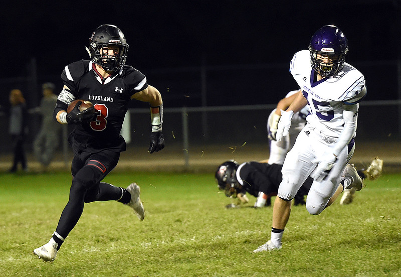 Loveland High's (3) Zachary Weinmaster takes the ball downfield for their second touchdown with Mountain View's (15) Kamden Carwin behind him Friday, Sept. 29, 2017, during their game at Patterson Stadium in Loveland. (Photo by Jenny Sparks/Loveland Reporter-Herald)