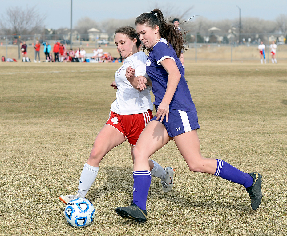 . Loveland\'s Riley Hall and Mountain View\'s Ainsely Wilson try to get to the ball during their soccer game Tuesday, March 12, 2019, at Mountain View High School in Loveland.  (Photo by Jenny Sparks/Loveland Reporter-Herald)
