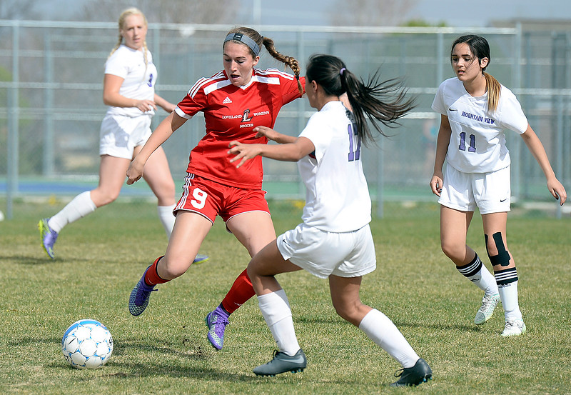 Loveland's #9 Maraia Rubin tries to get the ball past Mountain View's #17 Mayra Sanchez Pineda Monday, April 17, 2017, during their game at Mountain View High School.   (Photo by Jenny Sparks/Loveland Reporter-Herald)
