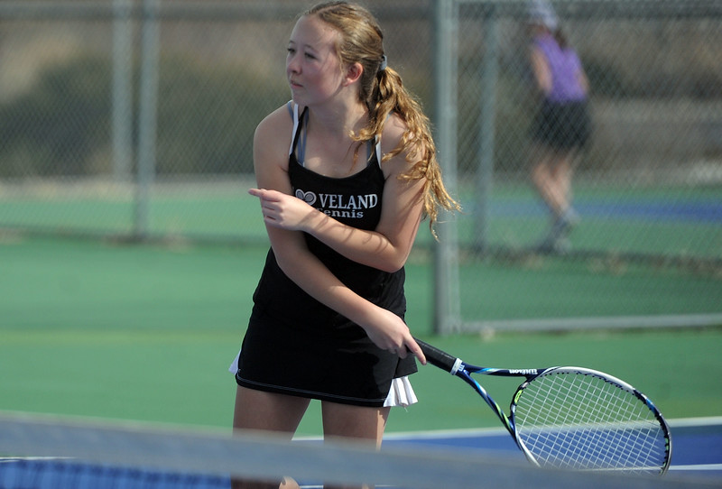 Loveland's Rebecca Emme finishes a shot against Mountain View's Kendall Kreiger at Mountain View's tennis courts on Tuesday, March 26. The Indians wons the match 7-0. (Colin Barnard/Loveland Reporter-Herald)