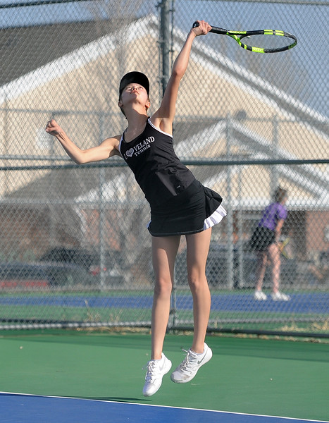 Loveland's Tara Jeffries rises during a serve against Mountain View's Sarah Gordon and Jaden Millward at Mountain View's tennis courts on Tuesday, March 26. The Indians wons the match 7-0. (Colin Barnard/Loveland Reporter-Herald)