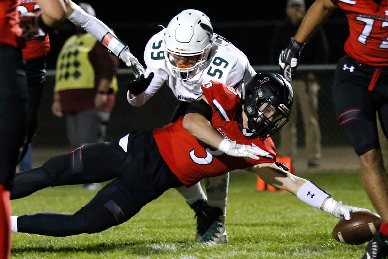 Loveland's Zachary Weinmaster (3) keeps a hold on the ball as Niwot's Jack Balsley (59) tackles him on Thursday, Oct. 12, 2017 at Patterson field. (Photo by Lauren Cordova/Loveland Reporter-Herland)