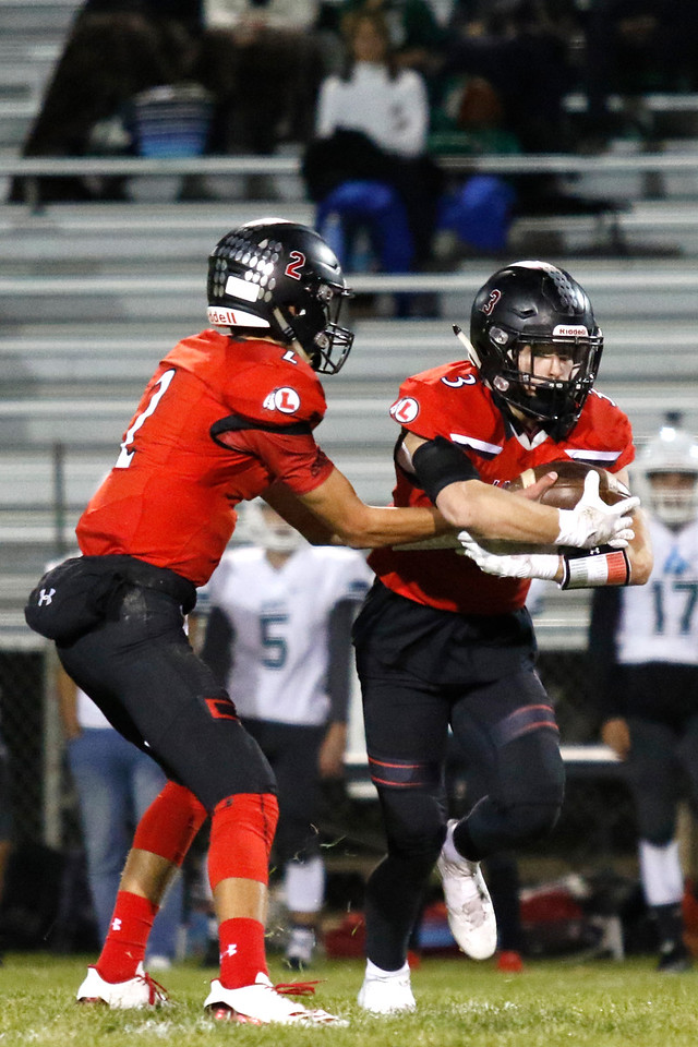 Loveland's Riley Kinney (2) hands off the ball to Zachary Weinmaster (3) on Thursday, Oct. 12, 2017 at Patterson field. (Photo by Lauren Cordova/Loveland Reporter-Herland)