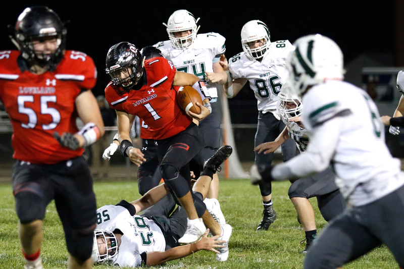 Loveland's Isaiah Meyers (1) pushes past Niwot's Lucas Steiner (58) attempted tackle on Thursday, Oct. 12, 2017 at Patterson field. (Photo by Lauren Cordova/Loveland Reporter-Herland)
