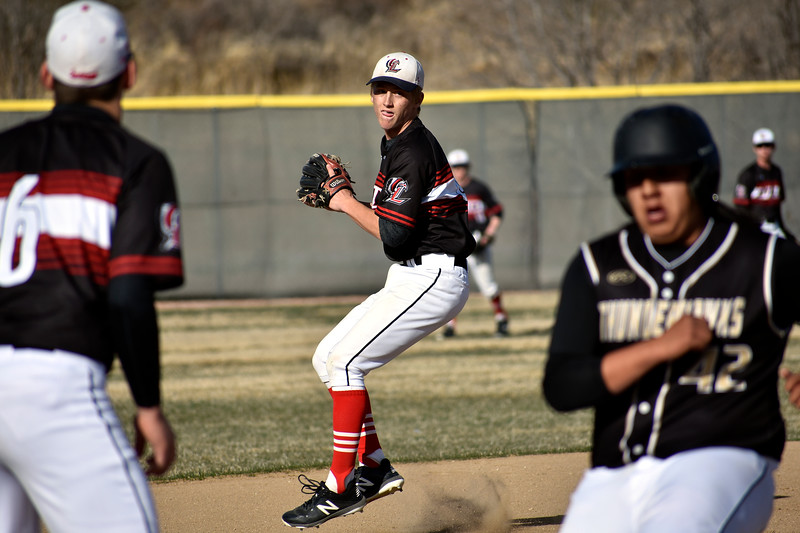 Loveland's (9) Tyler Hamill looks to throw the ball to his teammate (6) Jackson Bakovich at third base in order to tag Prairie View's (42) Terrance Barrios during their game on Tuesday, April 3, 2018 at Centennial Baseball Complex in Loveland. Photo by Thieng Mai/Loveland Reporter-Herald.