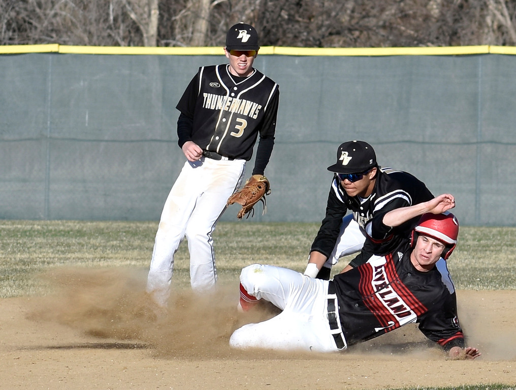 . Loveland\'s (2) Drew Massey attempts to slide into second base as Prairie View\'s (11, center) Dylan Baldizan and (3, left) Louis Lincoln tag him out during their game on Tuesday, April 3, 2018 at Centennial Baseball Complex in Loveland. Photo by Thieng Mai/Loveland Reporter-Herald.