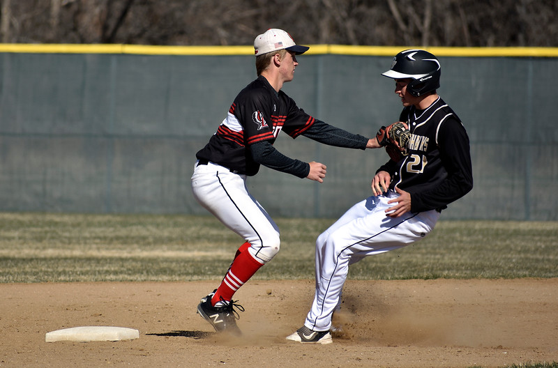 Loveland's (9) Tyler Hamill manages to stop Prairie View's (21) Brandon Skinner from reaching second base during their game on Tuesday, April 3, 2018 at Centennial Baseball Complex in Loveland. Photo by Thieng Mai/Loveland Reporter-Herald.