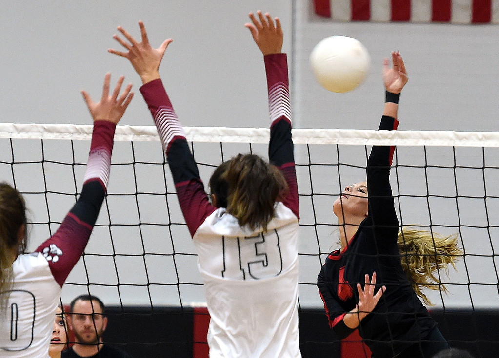 . Loveland\'s (4) Olivia Emerson spikes the ball as Rocky Mountain\'s (10) Hannah Kaufman and (13) try to block during their game Thursday, Oct. 18, 2018, at Loveland High School.  (Photo by Jenny Sparks/Loveland Reporter-Herald)