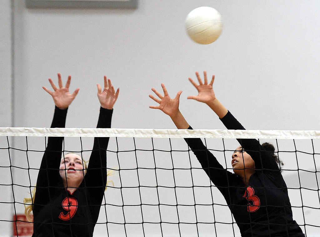 . Loveland\'s (9) Alexa Rodgers and (3) Lacy Hunt try to block the ball during their game against Rocky Mountain on Thursday, Oct. 18, 2018, at Loveland High School.  (Photo by Jenny Sparks/Loveland Reporter-Herald)