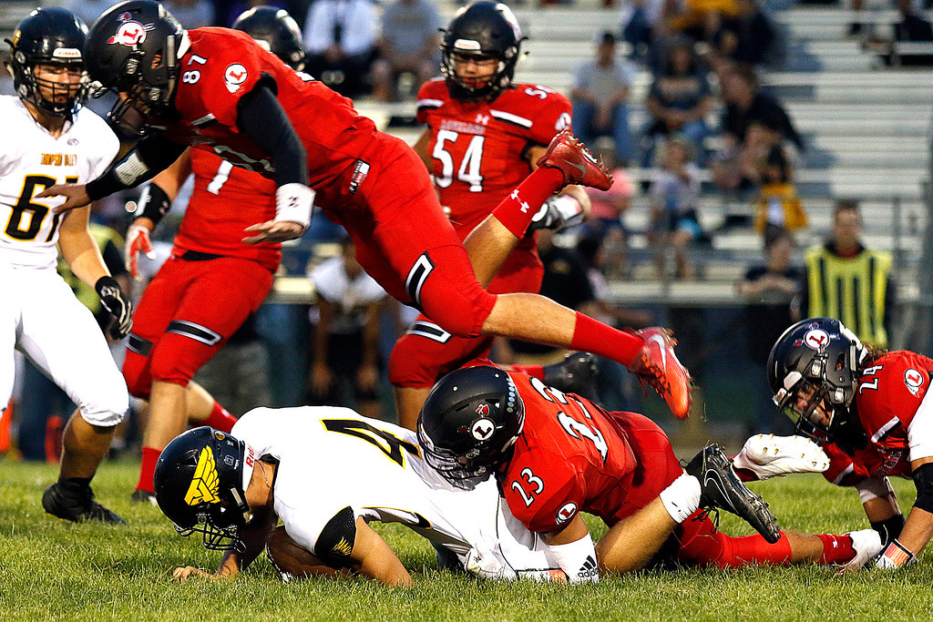 . Loveland�s Caleb Smith (23) tackles Thompson Valley�s Cameron Nellor (4) while Alex Seymour (87) jumps to assist Friday, Sept. 8, 2017 at Patterson Stadium in Loveland. (Photo by Lauren Cordova/Loveland Reporter-Herland)