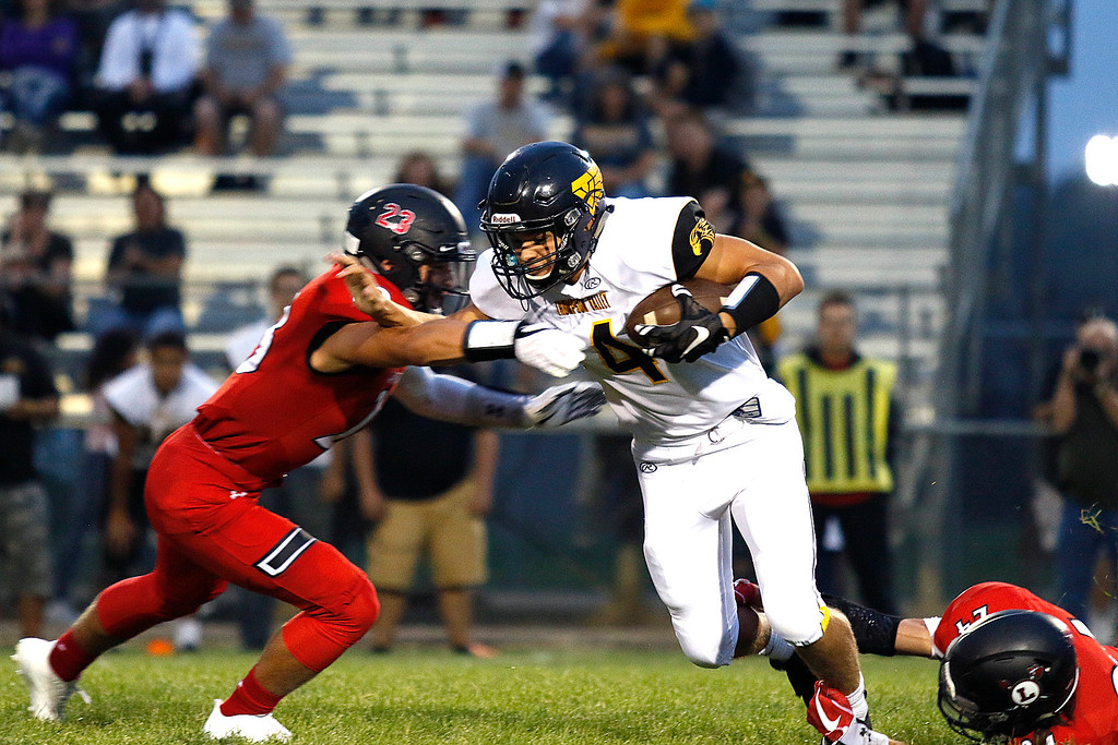 . Thompson Valley�s Cameron Nellor (4) pushes off Loveland�s Caleb Smith (23) while running the ball Friday. Sept. 8, 2017 at Patterson Stadium in Loveland. (Photo by Lauren Cordova/Loveland Reporter-Herald)