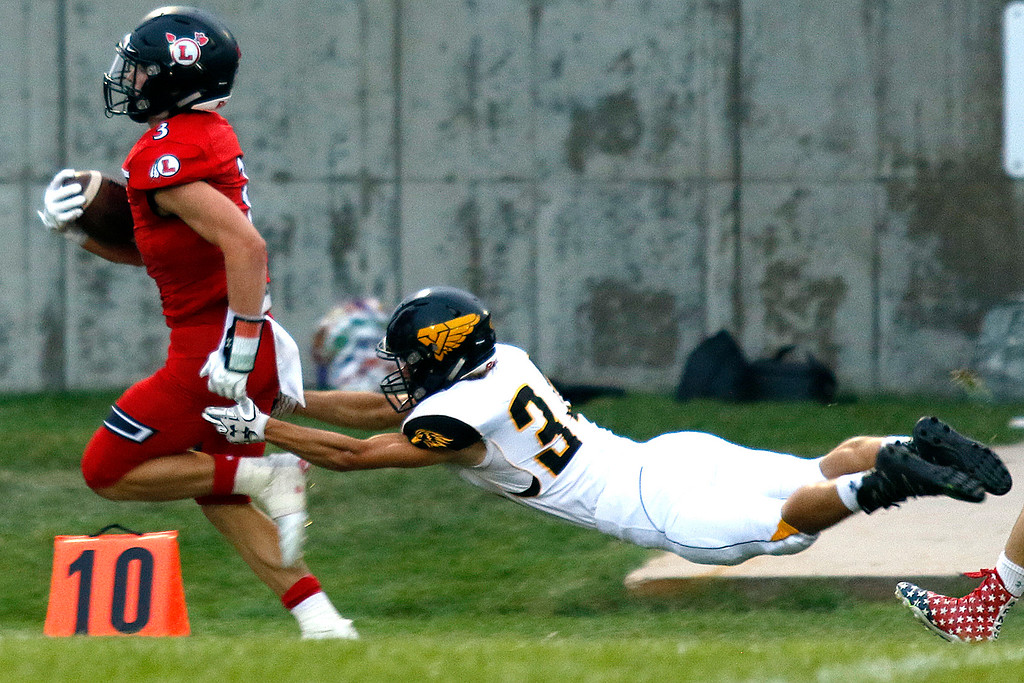 . Loveland�s Zach Weinmaster (3) runs to make a touchdown, avoinding Thompson Valley�s Wolfgang Warner (34) Friday, Sept. 8, 2017 at Patterson Stadium in Loveland. (Photo by Lauren Cordova/Loveland Reporter-Herland)