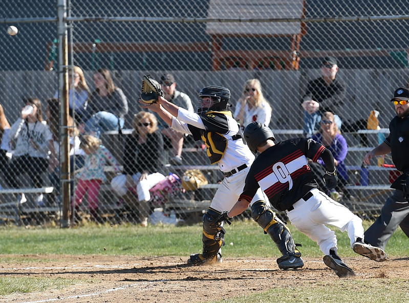 Loveland's #9 Tyler Hammil slides into home as Thompson Valley's catcher #11 Mike Berg catches the ball during their game Wednesday, April 5, 2017, at Thompson Valley high School in Loveland. (Photo by Jenny Sparks/Loveland Reporter-Herald)
