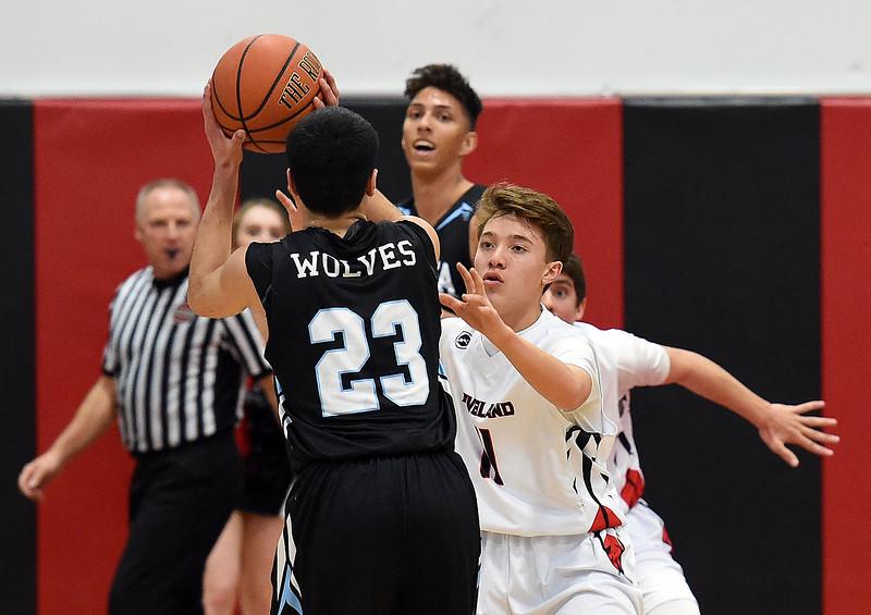 Loveland High's #11 Jaxon Cabrera tries to block Vista Ridge's #23 Julius Dowell during their game Tuesday, Dec. 12, 2017, at Loveland High School. (Photo by Jenny Sparks/Loveland Reporter-Herald)