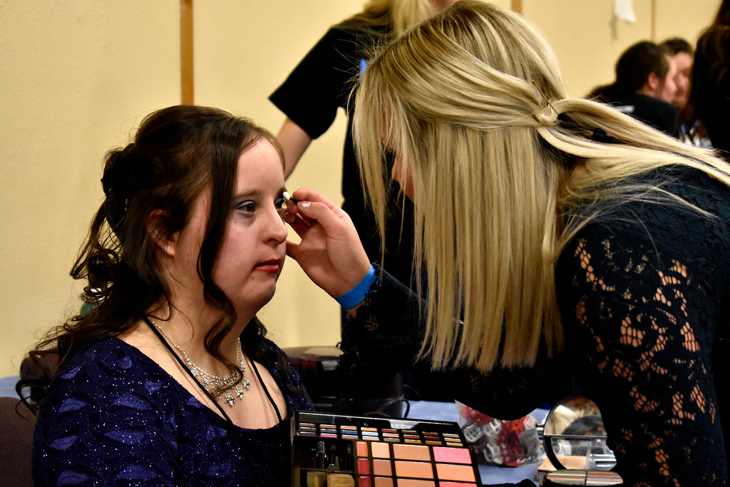 . Carrie Silk of Boulder gets herself a makeover from Riley Hyvonen of Parker before heading to the Night to Shine event at Grace Community Church in Loveland. Many different communities in Northern Colorado are involved in running the event every year. Photo by Thieng Mai/Loveland Reporter-Herald.
