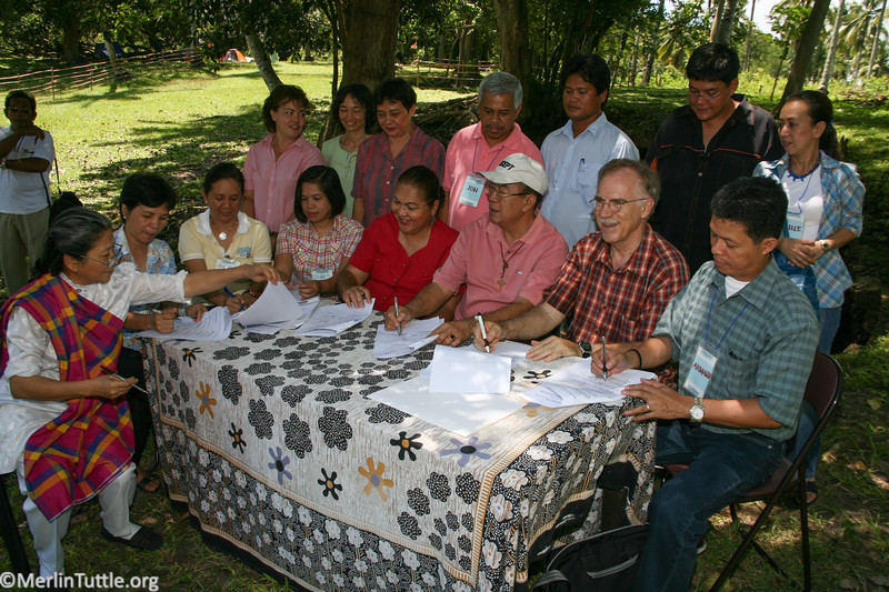Merlin with Norma Monfort (in red), local mayor, (with baseball cap) and local citizens sighning successful petition to Philippine Government to protect two million bats in the Monfort Bat Cave. Conservation