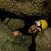 Merlin Tuttle crawling through a tight squeeze to reach remote gray myotis (Myotis grisescens) hibernation chamber in Hubbards Cave, Tennessee. Field Work