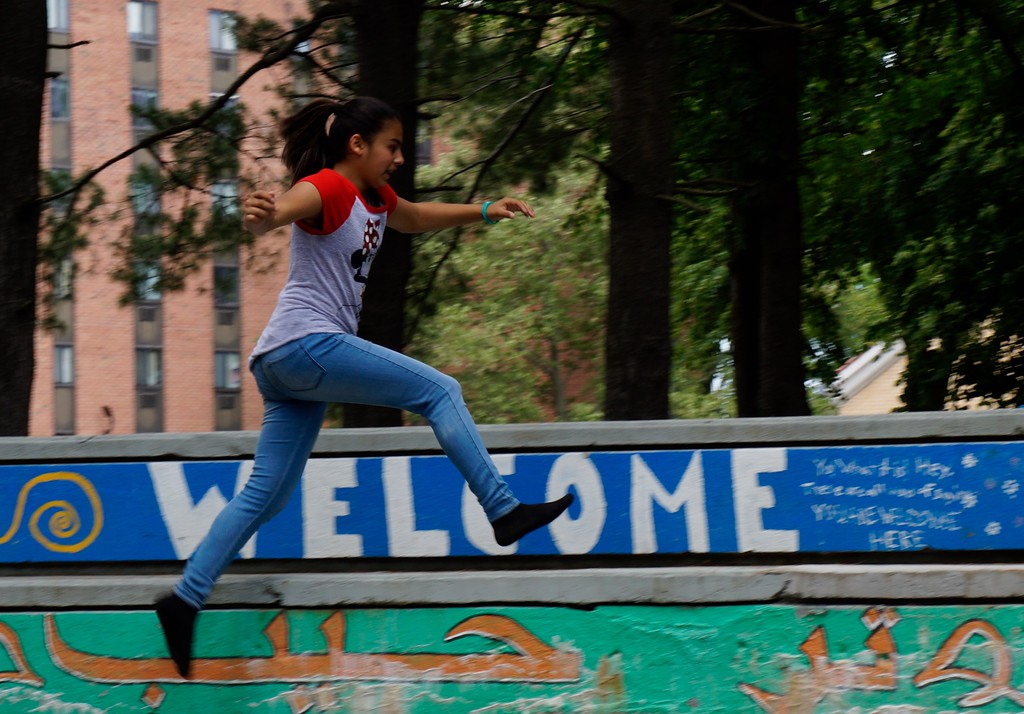 . Naydeliz Serrano, 13, of Lowell Ma. jumps on the stairs of Lowell�s Acre Fest Saturday, June 10th, 2017 in Lowell, Ma.  The stairs say welcome in many languages, and have transformed dramatically over the past few years. LOWELL SUN/KATIE DURKIN