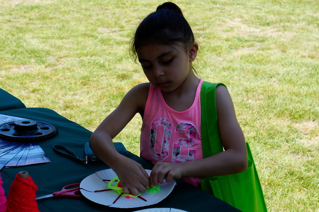 . Juliana Irizarry,8, of Lowell, Ma. practices circular weaving at the National Park�s tent during Lowell�s Acre Fest Saturday, June 10th, 2017 in Lowell, Ma.  LOWELL SUN/KATIE DURKIN