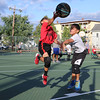 Evan Deleon of the Gators goes in for the shot while Miguel Arcila of the Celtics tried to stop him during the 7 to 9 year old Junior A League game at Father Maguire Park during the St. Jeanne Darc Summer basketball league. SUN/JOHN LOVE