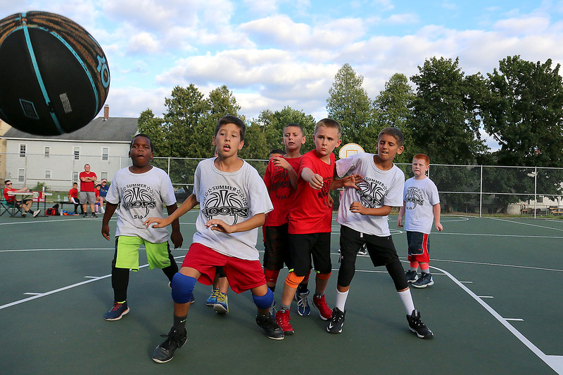 Players on the Celtics, in white, and Gators, in red, could not catch up to the ball as it went out of bounds during the 7 to 9 year old Junior A League game at Father Maguire Park during the St. Jeanne Darc Summer basketball league. SUN/JOHN LOVE