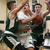 Lowell Catholic High School boys basketball player Keenan Rudy-Phol gets sandwiched between Austin Preparatory School players Aiden Beers and Peter Kelly as he tries to get the hoop during their game on Friday night. SUN/JOHN LOVE
