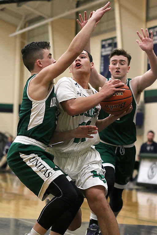 . Lowell Catholic High School boys basketball player Keenan Rudy-Phol gets sandwiched between Austin Preparatory School players Aiden Beers and Peter Kelly as he tries to get the hoop during their game on Friday night. SUN/JOHN LOVE