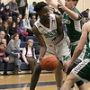 Lowell Catholic High School boys basketball player Brian Saroni tries to find an open teammate as he is covered by Austin Preparatory School player Denis Taylor during their game on Friday night. SUN/JOHN LOVE