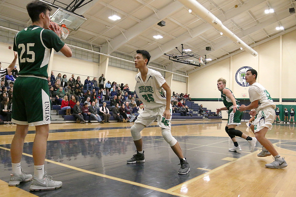 . Lowell Catholic High School boys basketball player Kai Yang covers Austin Preparatory School player Logan Bravo as he tries to inbound the ball during their game on Friday night. SUN/JOHN LOVE