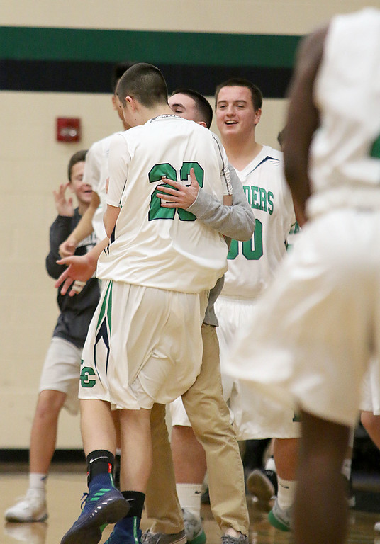 . Lowell Catholic High School boys basketball player Alex Ferriere gets congratulated by his coach after making a three pointer during a time out called by Austin Preparatory School on Friday night. SUN/JOHN LOVE