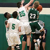 Lowell Catholic High School boys basketball player Caleb Scott tries to stop a shot by Austin Preparatory School player Stephen Reddy during their game on Friday night. SUN/JOHN LOVE