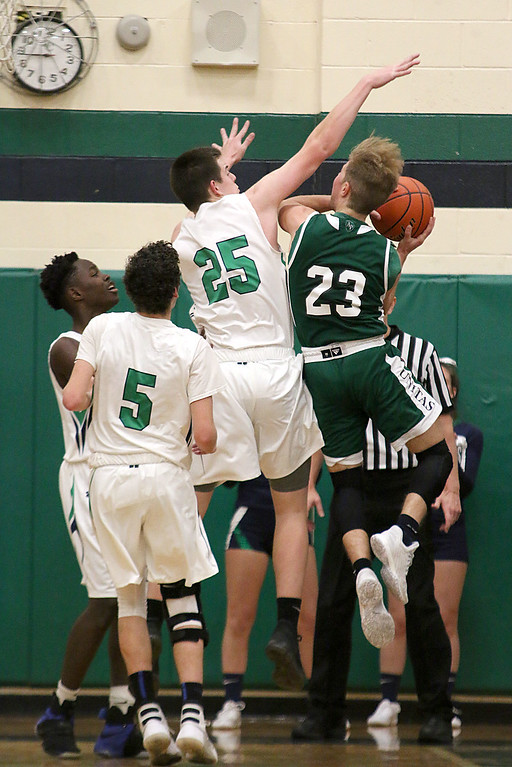 . Lowell Catholic High School boys basketball player Caleb Scott tries to stop a shot by Austin Preparatory School player Stephen Reddy during their game on Friday night. SUN/JOHN LOVE