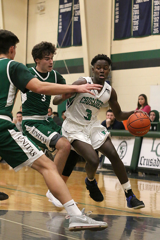 . Lowell Catholic High School boys basketball player Brian Saroni tries to get around Austin Preparatory School player Denis Taylor during action in their game on Friday night. SUN/JOHN LOVE