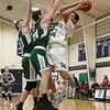 Lowell Catholic High School boys basketball player Keenan Rudy-Phol gets shot off over Austin Preparatory School players Ryan Andrews and Mitchell Kennedy during their game on Friday night. SUN/JOHN LOVE