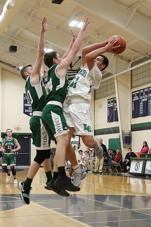 . Lowell Catholic High School boys basketball player Keenan Rudy-Phol gets shot off over Austin Preparatory School players Ryan Andrews and Mitchell Kennedy during their game on Friday night. SUN/JOHN LOVE