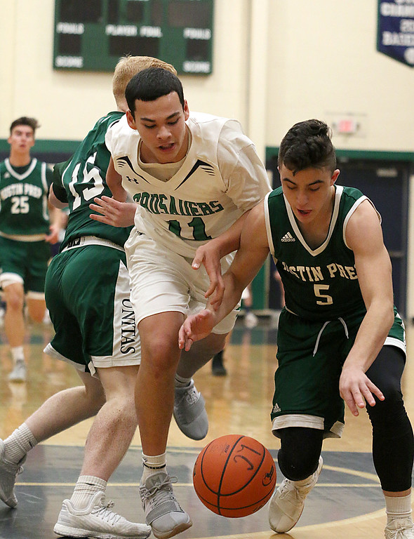 . Lowell Catholic High School boys basketball player Keenan Rudy-Phol and Austin Preparatory School player Aiden Beers go after a loose ball during their game on Friday night. SUN/JOHN LOVE
