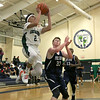 Lowell Catholic High School basketball played Pope John High School on Monday night in Lowell. LCHS player Isaiah Holmes puts up a shot by PJHS player Patrick Kelly. SUN/JOHN LOVE