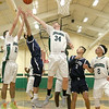 Lowell Catholic High School basketball played Pope John High School on Monday night in Lowell. LCHS player Davis Gill (21)and Liam Trainor (34) reach for a reabound as PJHS player Christian Hebert tries to get it before them. SUN/JOHN LOVE