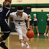Lowell Catholic High School basketball played Pope John High School on Monday night in Lowell. LCHS player Isaiah Holmes tries to get around PJHS player Dimmone Marshall during action in the game. SUN/JOHN LOVE