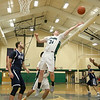 Lowell Catholic High School basketball played Pope John High School on Monday night in Lowell. Stretching for a rebound is LCHS player Liam Trainor during action in the game. SUN/JOHN LOVE