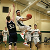 Lowell Catholic High School basketball played Pope John High School on Monday night in Lowell. LCHS player Isaiah Holmes goes around PJHS player Patrick Kelly as he goes in for a shot during action in their game. SUN/JOHN LOVE
