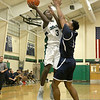 Lowell Catholic High School basketball played Pope John High School on Monday night in Lowell. LCHS player Brian Saroni tries to get off a shot as he is guarded by PJHS player Marques Bouyer. SUN/JOHN LOVE