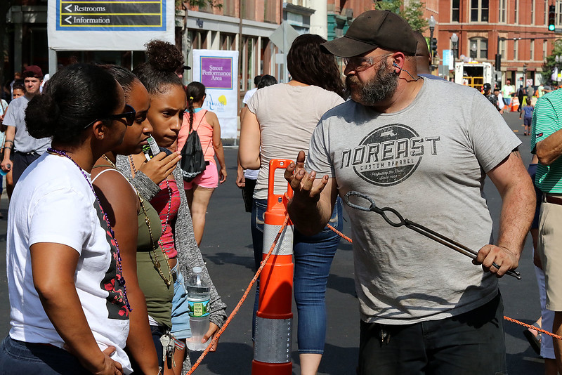 The last day of 2018 Folk Festival was packed with good food and great performances. Festival goers listen to blacksmith Rick Stec as he talks about how to make chain loops at his booth on Merrimack street during the festival. His booth was out in front if his business Red Antler Apothecary. LOWELL SUN/JOHN LOVE