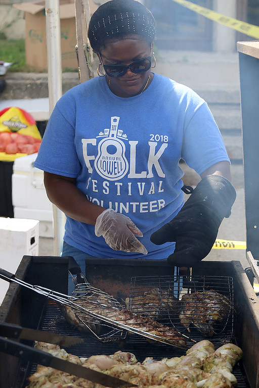 . The last day of 2018 Folk Festival was packed with good food and great performances. Chef Marie Accha cooks up some baked Tilapia during the festival. LOWELL SUN/JOHN LOVE