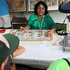 The last day of 2018 Folk Festival was packed with good food and great performances. Sunanda Sahay explains the painting, she was working on, from north India called Mithila at her booth at the festival on Sunday. LOWELL SUN/JOHN LOVE